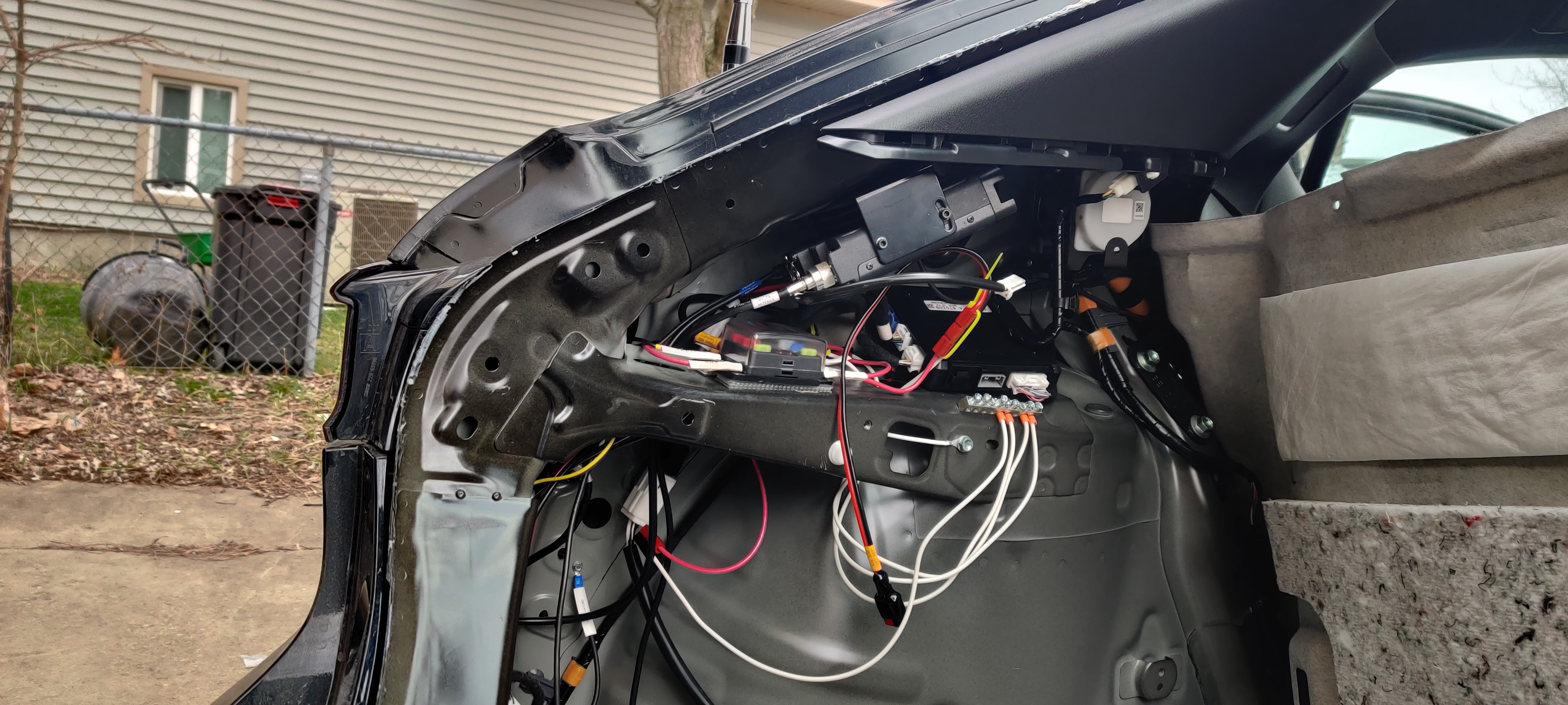 Completed installation, with coax labeled and terminated. The  backing plate for the mount is approximately behind the triangular gap formed by the FT-8900R and the OEM module. All access was through a narrow slit aft of the inner frame member, shown with a large knockout and the Breedlove grounding wire.